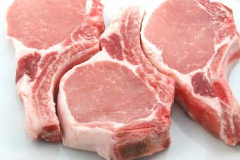 three plump center cut pork chops on white